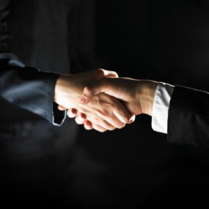 two people's hands shaking with suits on their arms