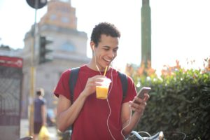 man with an orange drink in one hand laughing while looking at his cell phone in another hand.
