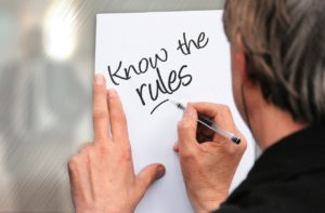 "caucasian man writing ""know the rules"" on a piece of paper pinned against the wall."