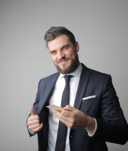 caucasian man in a suit with a card in one hand and the other holding his suit jacket