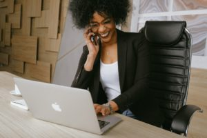 african american woman sitting in front of a laptop, holding a cellphone to her ear and laughing