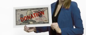 woman holding a large $50 bill with the word donation on it in red