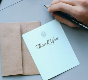 caucasian hand with a pen in it next to a white card that says thank you