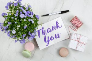 thank you note surrounded bu flowers, macarons, and a pen