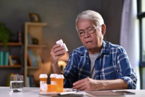 older asian man looking at a pill bottle in his hand with other bottles sitting on the table in front of him