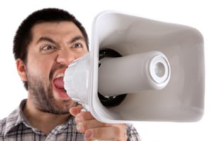 caucasian man yelling into a megaphone