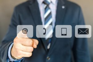 torso of a man in a suit pointing at an email button which is next to a phone button, tablet button and mail button.