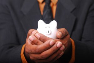 african american hands in a suit holding a white piggy bank.