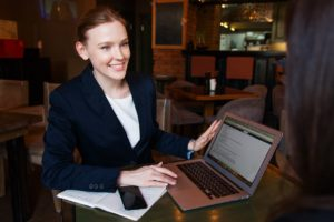 woman with a suit on smiling and holding her laptop