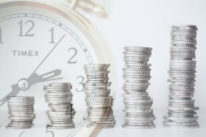 coins stacked going upwards and a clock in the background
