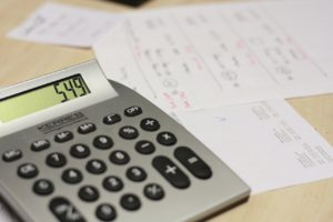 calculator with paper behind it on a desk